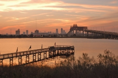 Sunset over the St. Johns River with dock and Matthews Bridge with downtown and Jaguars stadium in background