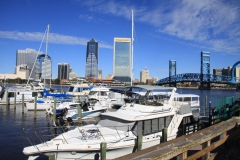 Boats docked near Main Street bridge with urban skyline