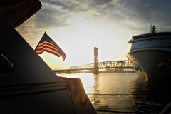 American flag blowing in wind off of stern of yacht while docked at Jacksonville Landing