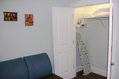 Clean open closet with fresh pillows and ironing board