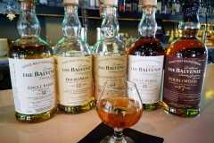 Row of premium Balvenie aged scotch with hald full brandy snifte