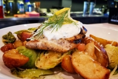 Grilled salmon with chives and potatoes topped with cream sauce