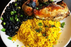 Plate of bbq chicken with rice and black beans