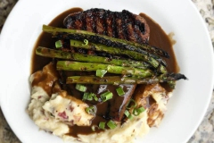 Filet mingion with grilled asparagas and garlic mashed potatoes in gravy